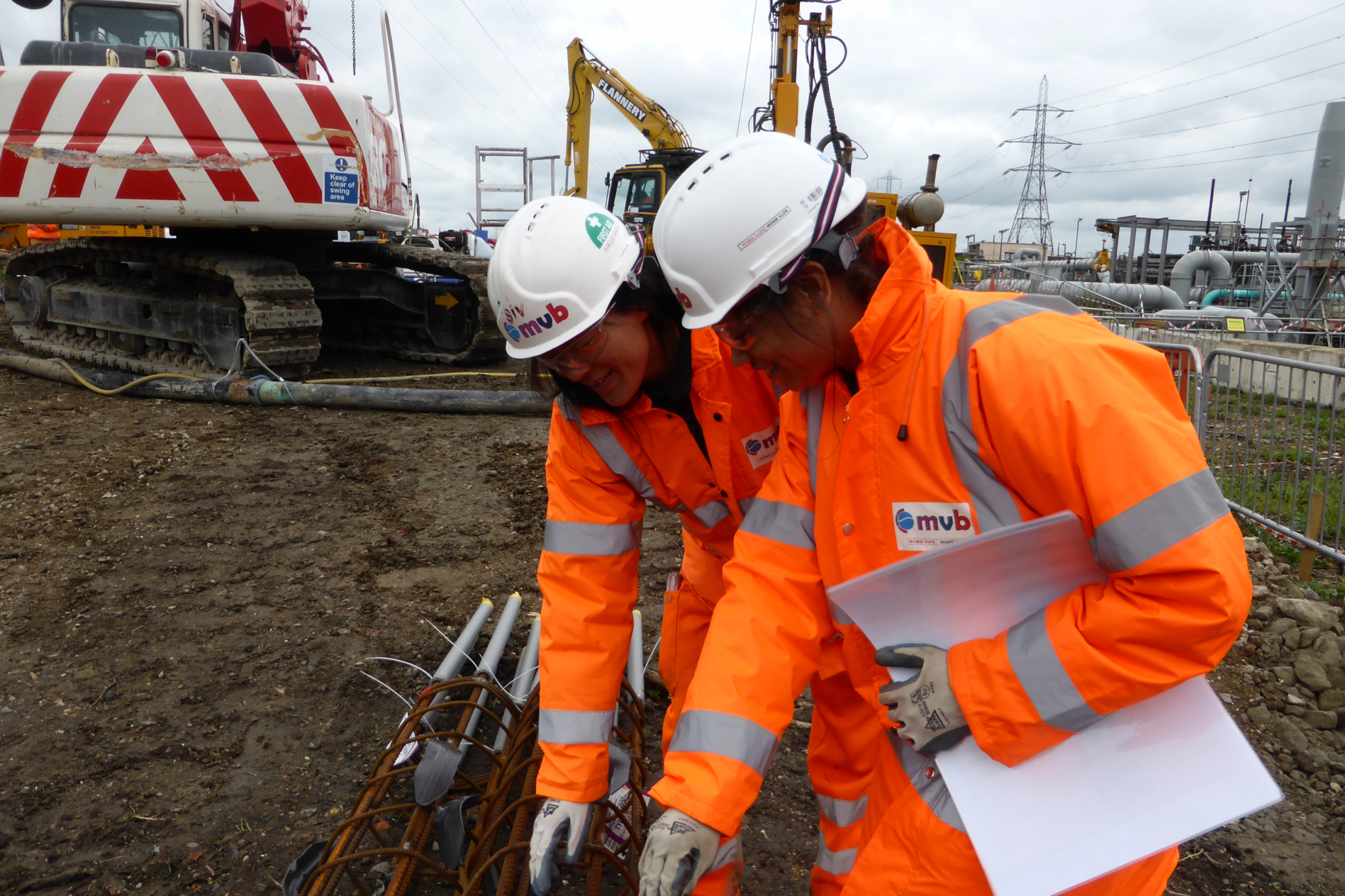 Sivilay Sayavong on site helping guide colleague in technical reinforcement detail in ppe